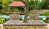ARALIA GARDEN DESIGN - PATRICIA FOX: WEDNESDAY HOUSE: WOODEN TREE SEAT WITH STONE WALL AND WOODEN LOGGIA NEXT TO SWIMMING POOL