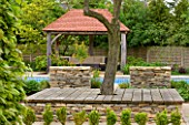 ARALIA GARDEN DESIGN - PATRICIA FOX: WEDNESDAY HOUSE: WOODEN TREE SEAT, STONE WALL, WOODEN LOGGIA AND SWIMMING POOL