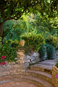 SICILY  ITALY: CASA CUSENI IN TAORMINA - ENTRANCE TO THE LOWER GARDEN WITH TERRACOTA TILED PATH  STEPS AND STONE WALL  RAISED BED  MEDITERRANEAN