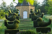 ROCKCLIFFE HOUSE, GLOUCESTERSHIRE: ROW OF CLIPPED TOPIARY BIRDS LEADING UP TO DOVECOTE. SUMMER, COUNTRY GARDEN, EVERGREEN, SHRUBS, SHAPED, TRIMMED