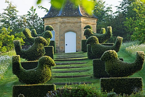 ROCKCLIFFE_HOUSE_GLOUCESTERSHIRE_ROW_OF_CLIPPED_TOPIARY_BIRDS_LEADING_UP_TO_DOVECOTE_SUMMER_COUNTRY_