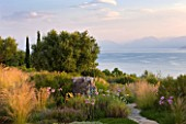 CORFU, GREECE - THE KASSIOPIA ESTATE:VIEW OUT TO SEA FROM THE TERRACE WITH PATH AND PLANTING SCHEME OF STIPA TENUISSIMA AND TULBAGHIA VIOLACEA