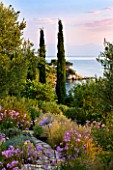 CORFU, GREECE - THE KASSIOPIA ESTATE: VIEW OUT TO SEA FROM GARDEN WITH STONE PATH,  STIPA TENUISSUIMA, TULBAGHIA VIOLACEA AND CYPRESS TREES