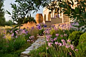 CORFU, GREECE - THE KASSIOPIA ESTATE: VIEW LOOKING UP TOWARDS VILLA WITH STONE URN, PATH AND PINK FLOWERS OF TULBAGHIA VIOLACEA