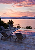 CORFU, GREECE - THE KASSIOPIA ESTATE: EVENING LIGHT - DUSK ON THE TERRACE LOOKING OUT TO SEA WITH SUN LOUNGERS. IN THE DISTANCE ARE THE ALBANIAN MOUNTAINS
