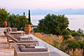CORFU, GREECE - THE KASSIOPIA ESTATE: THE SUN TERRACE WITH VIEW OUT TO SEA AND THE ALBANIAN MOUNTAINS IN THE DISTANCE
