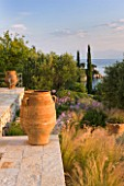 CORFU, GREECE - THE KASSIOPIA ESTATE: THE STONE TERRACE LOOKING OUT TO SEA WITH GARDEN, TERRACOTTA URNS AND OLIVE AND CYPRESS TREES