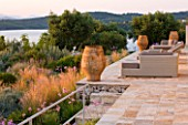 CORFU, GREECE - THE KASSIOPIA ESTATE: THE SUN TERRACE LOOKING OUT ONTO THE GARDEN WITH SEATING AREA, TERRACOTTA URNS AND VIEW OUT TO SEA