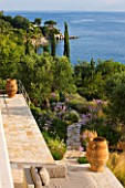 CORFU, GREECE - THE KASSIOPIA ESTATE: VIEW LOOKING DOWN ONTO THE GARDEN AND OUT TO SEA WITH STONE PATH, OLIVE TREES AND CYPRESS TREES