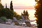 CORFU, GREECE - THE KASSIOPIA ESTATE: EVENING LIGHT - STONE TERRACE WITH SEATING AREA LOOKING OUT TO SEA AT DUSK