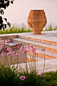 CORFU, GREECE - THE KASSIOPIA ESTATE: TERRACOTTA URN ON STONE TERRACE WITH PINK FLOWERS OF TULBAGHIA VIOLACEA