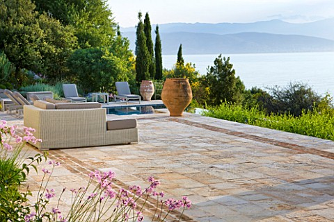 CORFU_GREECE__THE_KASSIOPIA_ESTATE_VIEW_OUT_TO_SEA_WITH_STONE_TERRACE_SEATING_AREA_AND_TERRACOTTA_UR