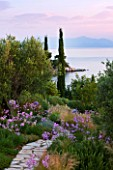 CORFU, GREECE - THE KASSIOPIA ESTATE: VIEW OUT TO SEA WITH STONE PATH, OLIVE AND CYPRESS TREE, STIPA TENUISSIMA AND TULBAGHIA VIOLACEA