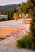 CORFU, GREECE - THE KASSIOPIA ESTATE: STONE TERRACE WITH SEATING AREA, HUGE STONE URN AND PINK FLOWERS OF TULBAGHIA VIOLACEA WITH BOUGAINVILLEA