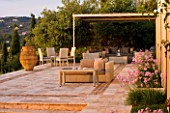 CORFU, GREECE - THE KASSIOPIA ESTATE: STONE TERRACE WITH SEATING AREA, HUGE STONE URN AND PINK FLOWERS OF TULBAGHIA VIOLACEA