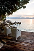 CORFU, GREECE - THE KASSIOPIA ESTATE: VIEW LOOKING OUT TO SEA AT SUNSET ON DECKED TERRACE WITH RATTAN CHAIRS. ALBANIAN MOUNTAINS IN THE DISTANCE