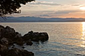 CORFU, GREECE - THE KASSIOPIA ESTATE: VIEW OF THE BAY LOOKING OUT TO SEA AT SUNSET WITH ALBANIAN MOUNTAINS IN THE DISTANCE