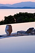 CORFU, GREECE - THE KASSIOPIA ESTATE. VIEW OF POOL TERRACE LOOKING OUT TO SEA AT DUSK WITH TERRACOTTA URN AND SUN LOUNGER. IN THE DISTANCE ARE THE ALBANIAN MOUNTAINS