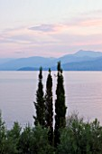 CORFU, GREECE - THE KASSIOPIA ESTATE. VIEW LOOKING OUT TO SEA WITH CYPRESS TREES AND THE ALBANIAN MOUNTAINS IN THE DISTANCE