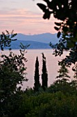 CORFU, GREECE - THE KASSIOPIA ESTATE. VIEW OUT TO SEA AT SUNSET WITH CYPRESS AND OLIVE TREES WITH ALBANIAN MOUNTAINS IN THE DISTANCE