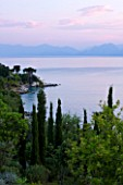 CORFU, GREECE - THE KASSIOPIA ESTATE. VIEW OF THE BAY LOOKING OUT TO SEA WITH OLIVE AND CYPRESS TREES AND ALBANIAN MOUNTAINS IN THE DISTANCE