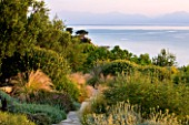 CORFU, GREECE - THE KASSIOPIA ESTATE. VIEW OF GARDEN LOOKING OUT TO SEA FROM THE VILLA WITH STONE PATH AND STIPA TENUISSIMA