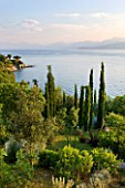 CORFU, GREECE - THE KASSIOPIA ESTATE. VIEW OUT TO SEA WITH ALBANIAN MOUNTAINS IN THE DISTANCE WITH OLIVE AND CYPRESS TREES. MEDITERRANEAN.