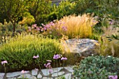 CORFU,GREECE-THE KASSIOPIA ESTATE.THE GARDEN WAS DESIGNED BY JENNIFER GAY, USING STONE AND A NATURALISTIC PLANTING SCHEME.WITH STIPA TENUISSIMA AND TULBAGHIA VIOLACEA.HOT,DRY