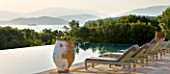 CORFU, GREECE - THE KASSIOPIA ESTATE. THE TERRACE AND SWIMMING POOL WITH SUN LOUNGERS AND TERRACOTTA URNS WITH VIEW OUT TO SEA