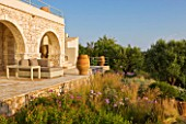 CORFU, GREECE - THE KASSIOPIA ESTATE. THE TERRACE WITH SUN LOUNGERS, TERRACOTTA URNS AND PLANTING BY JENNIFER GAY.