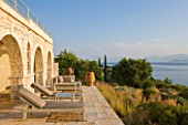 CORFU, GREECE - THE KASSIOPIA ESTATE. THE TERRACE WITH SUN LOUNGERS, TERRACOTTA URNS AND PLANTING BY JENNIFER GAY, LOOKING OUT TO SEA