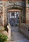 BIRTSMORTON COURT, WORCESTERSHIRE: VIEW THROUGH ARCHWAY ACROSS THE BRIDGE TO THE COURTYARD BESIDE THE COURT IN SUMMER