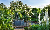 BIRTSMORTON COURT, WORCESTERSHIRE: WHITE GARDEN - LEAD POOL / POND WITH CHERUB FOUNTAIN, WHITE DELPHINIUMS AND METAL ARCH WITH ROSE ICEBERG. COUNTRY GARDEN, CLASSIC, ENGLISH