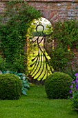 BIRTSMORTON COURT, WORCESTERSHIRE: THE ANGEL GATE IN THE WALLED GARDEN LOOKING OVER THE MALVERN HILLS. MADE BY MIKE ROBERTS, WALL, ENGLISH GARDEN, EVENING LIGHT, DUSK, ORNAMENT