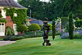 POULTON HOUSE GARDEN, WILTSHIRE: HOUSE AND LAWN WITH WITH ABSTRACT BRONZE SCULPTURE CHAIN OF EVENTS BY TONY CRAGG - IRISH YEWS - COUNTRY GARDEN, SUMMER, GREEN