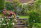 POULTON HOUSE GARDEN, WILTSHIRE: THE WALLED ROSE GARDEN - BRICK STEPS LEADING UP TO LAWN WITH ROSES - ROSES ON PERGOLAS - COUNTRY GARDEN, SUMMER. CLIMBING ROSES