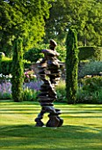 POULTON HOUSE GARDEN, WILTSHIRE: LAWN WITH IRISH YEWS AND ABSTRACT BRONZE STATUE / SCULPTURE CALLED CHAIN OF EVENTS BY TONY CRAGG