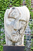 POULTON HOUSE GARDEN, WILTSHIRE: STONE SCULPTURE OF FACE IN WALLED GARDEN - MARBLE SCULPTURE - HERACLITUS - BY EMILY YOUNG