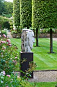 POULTON HOUSE GARDEN, WILTSHIRE: GRAVEL PATH LEADS AROUND THE EDGE OF THE WALLED GARDEN WITH CLIPPED QUERCUS ILEX TREES - MARBLE SCULPTURE - HERACLITUS - BY EMILY YOUNG