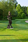 POULTON HOUSE GARDEN, WILTSHIRE: THE LAWN BETWEEN THE RILLS AND MAIN DRIVE WITH ABSTRACT BRONZE SCULPTURE CHAIN OF EVENTS BY TONY CRAGG