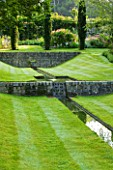 POULTON HOUSE GARDE, WILTSHIRE: WATER FEATURE. A DESCENDING FLIGHT OF RILLS SET INTO SUNKEN LAWN WITH JUNIPER TREES
