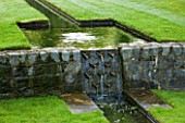 POULTON HOUSE GARDEN, WILTSHIRE: WATER FEATURE. DETAIL OF A DESCENDING FLIGHT OF RILLS SET INTO SUNKEN LAWN, WITH WATER CASCADE