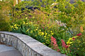 HORATIOS GARDEN  SALISBURY HOSPITAL  WILTSHIRE - DESIGNER CLEEVE WEST - LIMESTONE WALL WITH BORDER OF ACHILLEA MOONSHINE  CENTRANTHUS RUBER AND KNAUTIA MACEDONICA