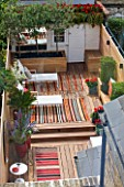 BEN DE LISI HOUSE AND GARDEN, LONDON: VIEW ONTO GARDEN WITH CARPETS, DECKING, DECK CHAIRS, SHED, LOUNGERS, SMALL GARDEN, TOWN GARDEN, OUTDOOR LIVING, SUMMER, DECKED, TERRACE, PATIO