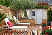 BEN DE LISI HOUSE AND GARDEN, LONDON: BACK GARDEN WITH CARPETS, DECKING, DECK CHAIRS, SHED, LOUNGERS, SMALL GARDEN, TOWN GARDEN, OUTDOOR LIVING, SUMMER, DECKED, TERRACE, PATIO