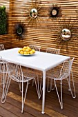 BEN DE LISI HOUSE AND GARDEN  LONDON: WHITE ALUMINIUM CHAIRS AND TABLE WITH PORCELAIN ENAMELLED STEEL TOP  FRENCH SIXTIES SUNBURST MIRRORS ON WALL