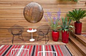 BEN DE LISI HOUSE AND GARDEN  LONDON: BRAZILIAN HARDWOOD DECKING  RED CONTAINERS WITH PEROVSKIA  AGAVE AND FERN  TABLE AND CHAIRS  COPPER BEATEN DISC ON WALL