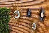 BEN DE LISI HOUSE AND GARDEN  LONDON: FRENCH SIXTIES SUNBURST MIRRORS ON WALL IN THE GARDEN