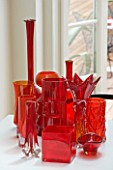 BEN DE LISI HOUSE AND GARDEN  LONDON: TABLE IN KITCHEN WITH COLLECTION OF RED GLASS AND VINTAGE MURANO PIECES