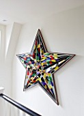 BEN DE LISI HOUSE AND GARDEN  LONDON: DECORATIVE STAR SCULPTURE ON WALL BY STAIRCASE